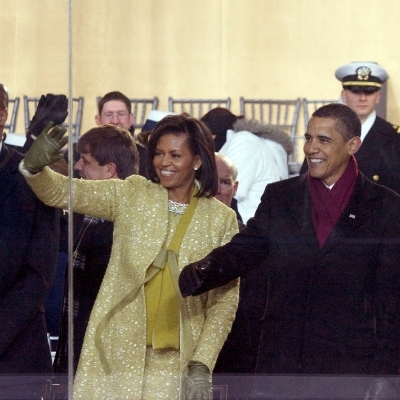 barack and michelle obama wave to a crowd