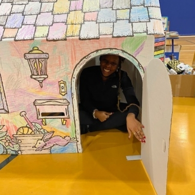 a woman smiles from within a colored cardboard house